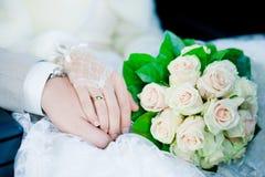 手和圆环在婚礼花束 库存图片