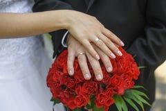 手和圆环新娘和新郎在婚礼花束 免版税库存图片
