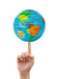 手和转动的地球 库存照片