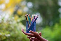 手和铅笔在许多颜色 库存图片