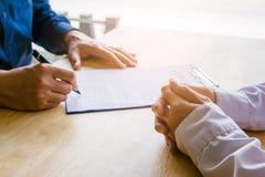 手回顾和签字在纸的候宰栏的亚洲事务 库存图片