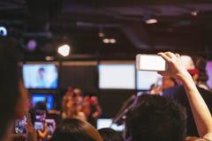 手固定的单元电话黑屏照片射击迷离音乐会 免版税库存照片
