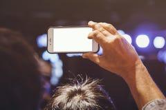 手固定的单元电话黑屏照片射击迷离音乐会 免版税图库摄影