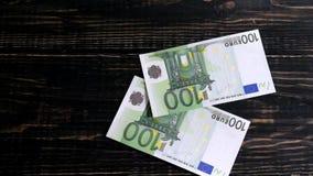手在一张木桌上把500欧元放 股票视频