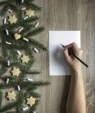 手在一张白色纸片写一支黑铅笔,并且在右边在一张木桌上的云杉的分支和蛋白软糖, 库存照片