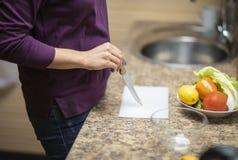 手在厨房里切开沙拉的菜 免版税库存照片