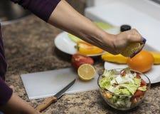 手在厨房里切开沙拉的菜 免版税库存图片