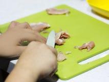手在厨房里砍了在一个绿色委员会的鸡内圆角 库存图片