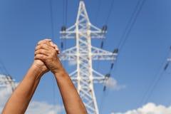 手在同意和主输电线横渡了反对蓝色 免版税库存图片