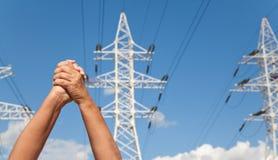 手在同意和主输电线横渡了反对蓝色 免版税库存照片
