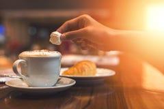手在咖啡上的举行蛋白软糖 免版税库存图片