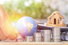 手在堆的被投入的金钱硬币、地球和房子、概念在成长,出售、购买、救球和investt在事务 库存图片