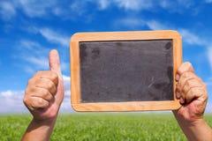 手在天空中的拿着一个空白石板黑板 免版税库存照片