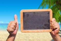 手在天空中的拿着一个空白石板黑板 图库摄影
