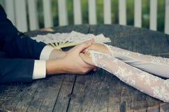 手在婚礼夫妇的手上。爱恋的关心 库存图片