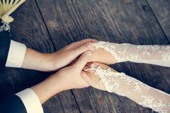 手在婚礼夫妇的手上。爱恋的关心 免版税图库摄影