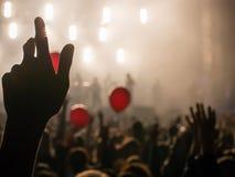 手在摇滚乐音乐会期间的天空中现出轮廓反对明亮的光 免版税图库摄影