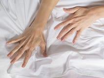 手在旅馆客房抓住掌握白色被弄皱的床单,销魂的标志,感觉乐趣或性交高潮 免版税库存照片