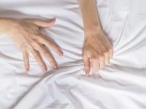 手在旅馆客房抓住掌握白色被弄皱的床单,销魂的标志,感觉乐趣或性交高潮 免版税库存图片