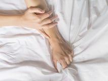 手在旅馆客房抓住掌握白色被弄皱的床单,销魂的标志,感觉乐趣或性交高潮 库存照片