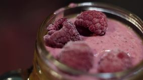手在桃红色大量上表面把有些莓放在玻璃瓶子作为装饰 股票视频