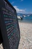手在海滩的书面菜单在希腊语Taverna之外 库存图片