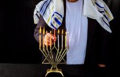 手在犹太教灯台犹太假日hannukah标志的燃烧蜡烛 库存图片