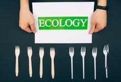 任意塑料 o 手在环境友好的自然和单一用处叉子附近拿着与词生态的纸 ?? 库存图片