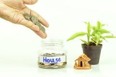 手在瓶上把金钱放对为房子,在成长,出售的概念保存 免版税库存图片