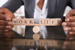 手在生活和工作之间的覆盖物平衡在跷跷板 免版税库存照片