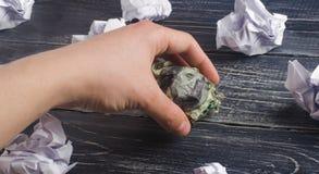 手在白皮书球的手上采取一被弄皱的美元 认为和发现新的企业想法的过程,有益 免版税库存照片