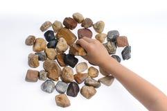 手在白色背景的举行石头 免版税库存照片