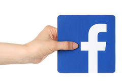手在白色背景的纸对facebook商标负打印 免版税库存照片