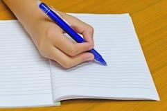 手在笔记薄,学生写 免版税库存照片