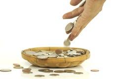 手在篮子投入了硬币金钱 免版税图库摄影