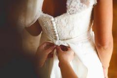手在精美新娘的腰部上把弓放 免版税图库摄影