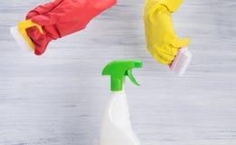 手在红色和黄色,橡胶手套拿着刷子和在瓶旁边到浪花清洁产品,在灰色背景 库存图片