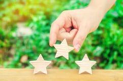 手在绿色背景上把第三个星放 质量评估和大众化 餐馆或旅馆概要 Awardi 免版税库存图片