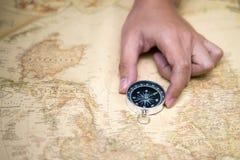 手在老地图的抓住指南针 免版税库存照片
