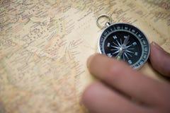 手在老地图的抓住指南针 库存照片