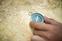 手在老地图的抓住指南针 图库摄影