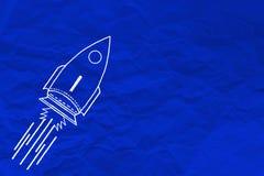 手在蓝色被弄皱的纸的文字火箭 免版税库存照片