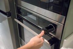 手在银色黑墙壁烤箱的紧迫按钮与固定mic 免版税库存图片