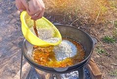 手在露天烹调的肉饭一口大大锅投入了米在一个晴天 一个水平的框架 库存图片