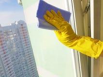 手在黄色与一块蓝色旧布玻璃的手套国内家庭洗衣机房子窗口里 库存照片