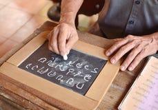 手在黑板的文字字母表 免版税图库摄影