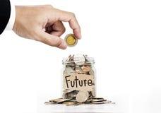 手在玻璃瓶子投入了硬币,存金钱为未来,在白色背景 免版税库存照片