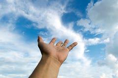 手培养请求在天空 库存图片