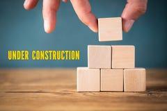 手堆积空白的立方体和消息'建设中' 免版税库存图片