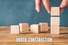 手堆积空白的立方体和消息'建设中' 库存图片